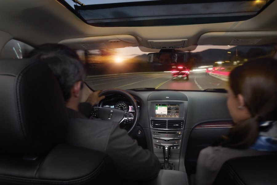 A couple is seen driving a Lincoln M K T while brake lights of the car in front of them are seen through the windshield.