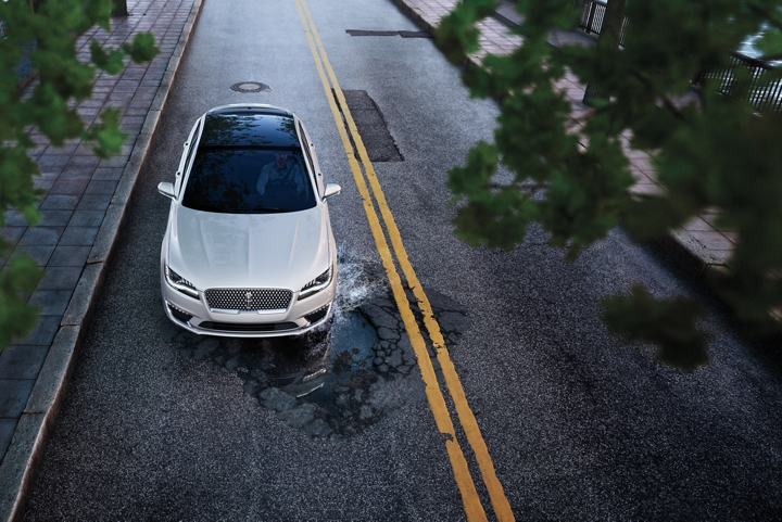 A 2020 Lincoln M K Z seen using its adaptive suspension to help reduce the jarring effects of a pothole