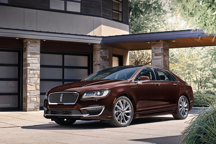 The 2020 Lincoln M K Z shown in Magma Red is shown parked in the driveway of an elegant home
