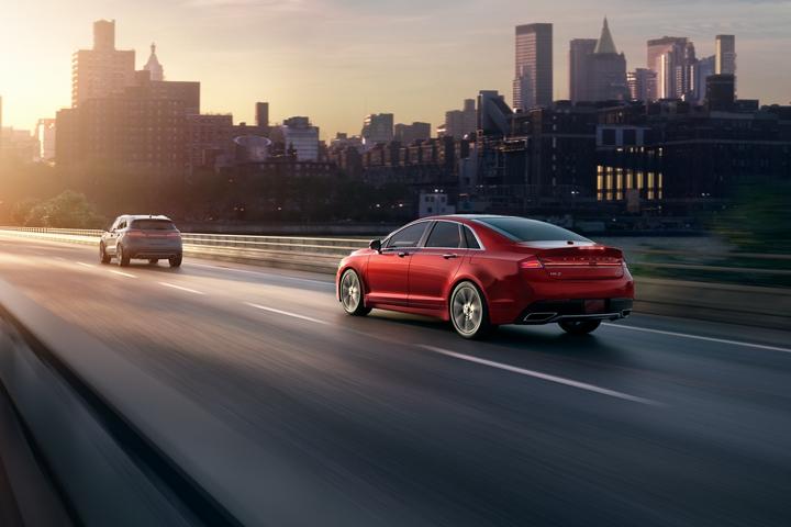 Se muestra un Lincoln M K Z 2020 en el color exterior alfombra roja andando por una carretera bajo la puesta del sol