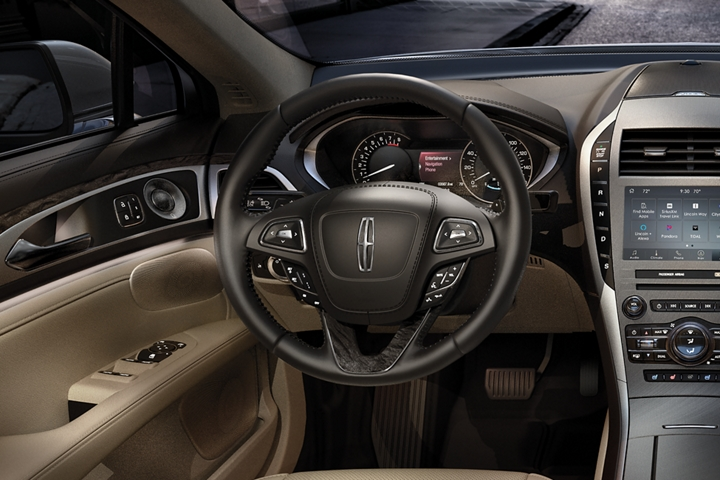 The leather wrapped 2020 Lincoln M K Z steering wheel seen with sunlight bouncing off the in wheel controls