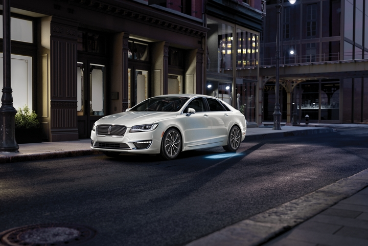 A patch of light resembling the Lincoln logo illuminates on the ground from a 2020 Lincoln M K Z