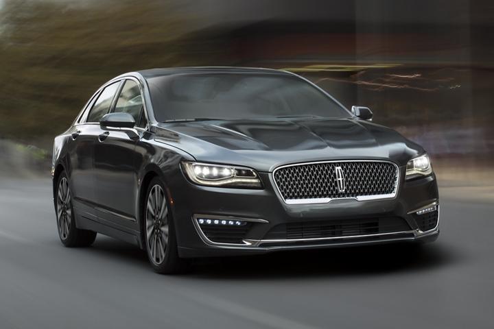 Se muestra un Lincoln M K Z 2020 en el color exterior negro infinito andando por un paisaje urbano