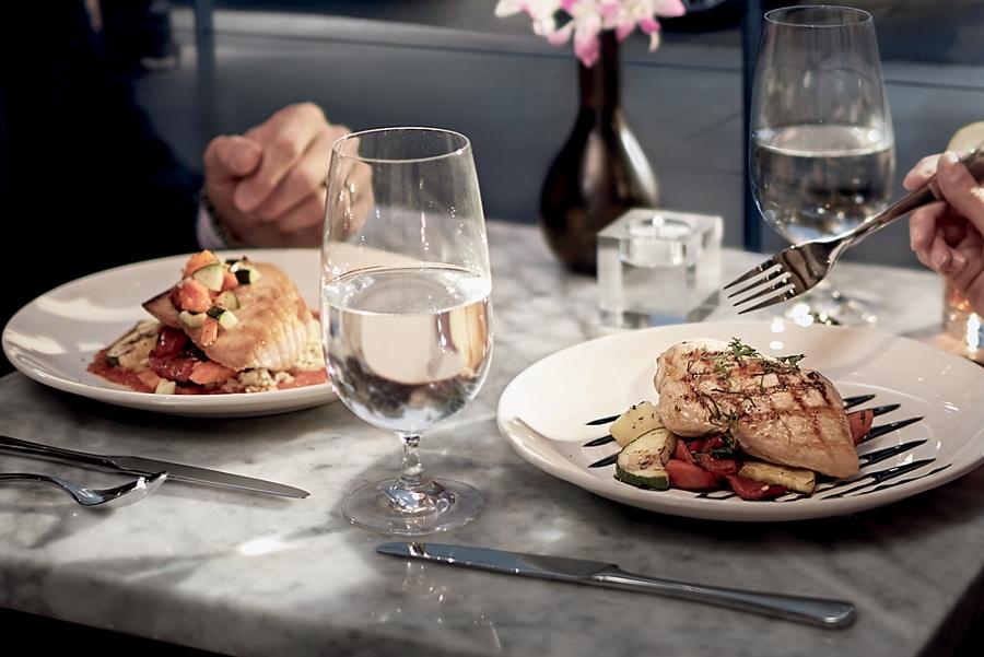 Se muestran dos personas disfrutando de una suntuosa comida en un restaurante fino
