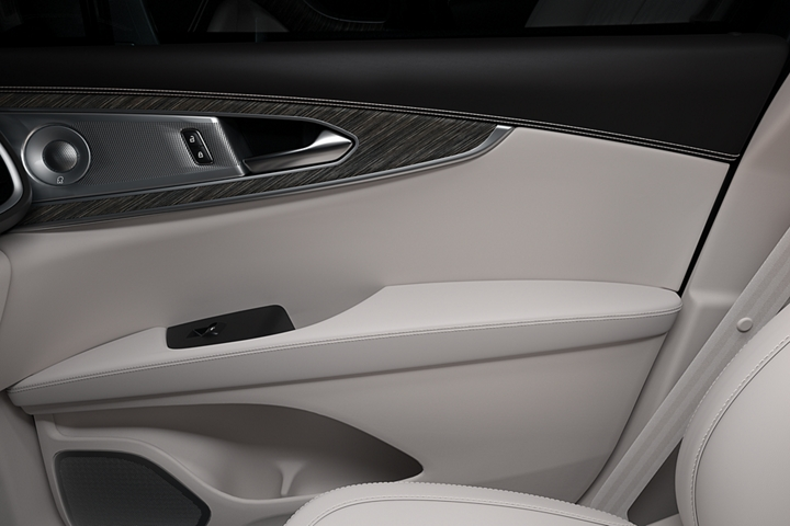 The inside of the front passenger door is shown with rich leather and real wood inlays