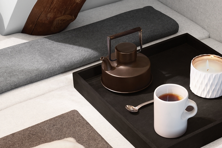 A tea kettle a tea cup and a lit candle are shown on a tea tray to reflect the calming nature of the Chalet theme