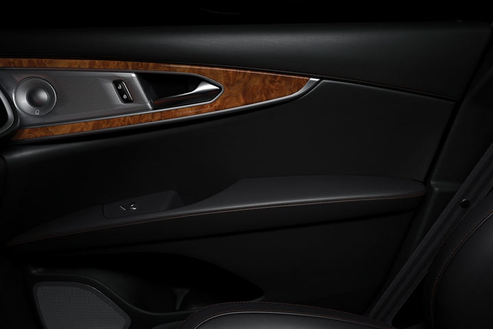 The front passenger door is shown from the interior highlighting dark leather and rich real wood inlays