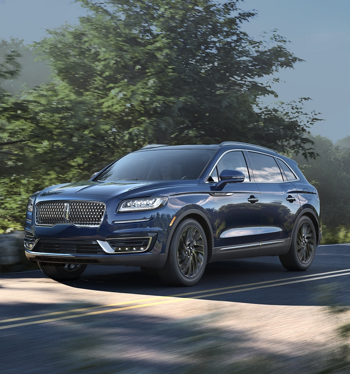A 2020 Lincoln Nautilus is shown in the rhapsody blue color being driven down a country road