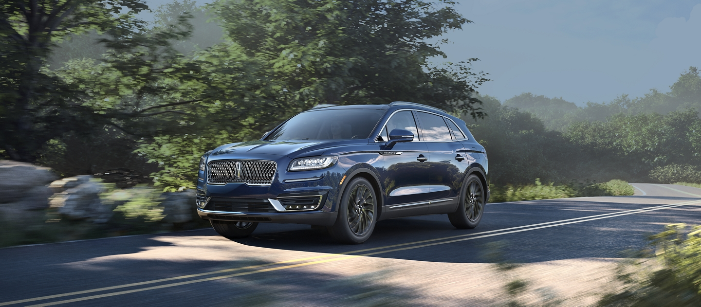 A 2020 Lincoln Nautilus shown in the rhapsody blue exterior color is being driven down a country road