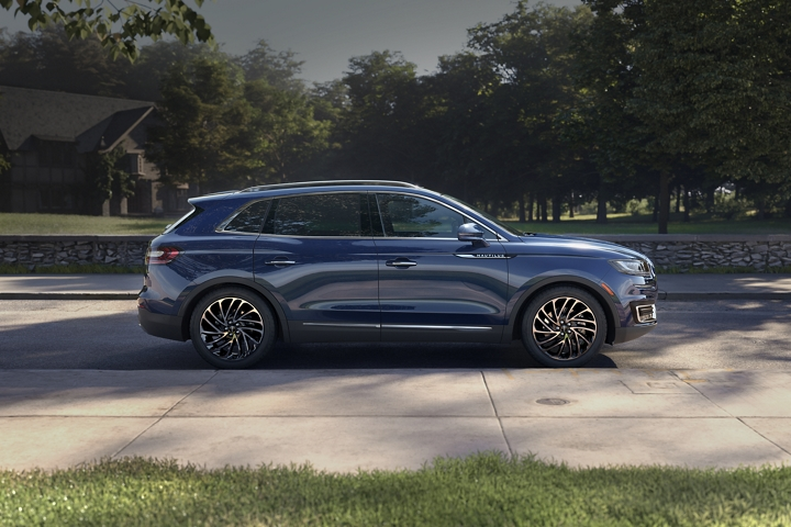 A 2020 Lincoln Nautilus in the Rhapsody Blue exterior color is shown parked on a street in a neighborhood