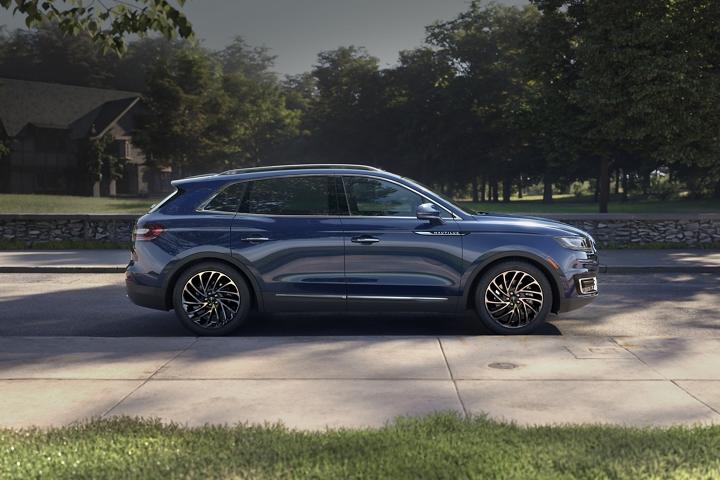 Imagen de la Lincoln Nautilus 2020 cuyo color exterior es azul Rhapsody estacionado en la calle de un vecindario