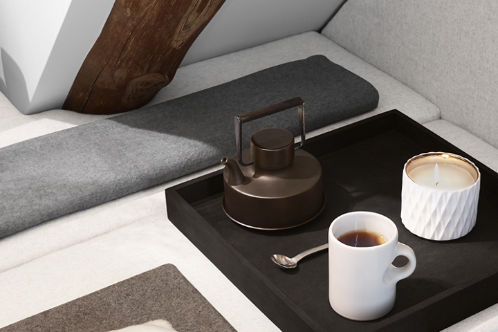 A tea kettle tea cup and a lit candle are shown on a tea tray to reflect the calming nature of the Chalet theme