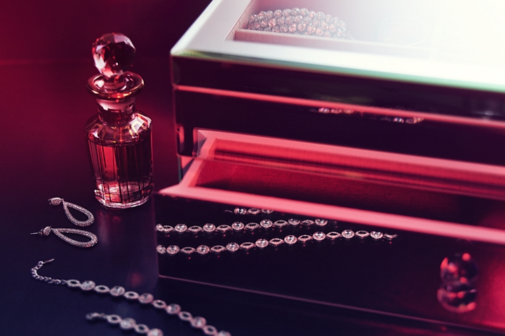 In this image perfume and jewelry are laid out on a dressing table to represent the inspiration for the Gala theme