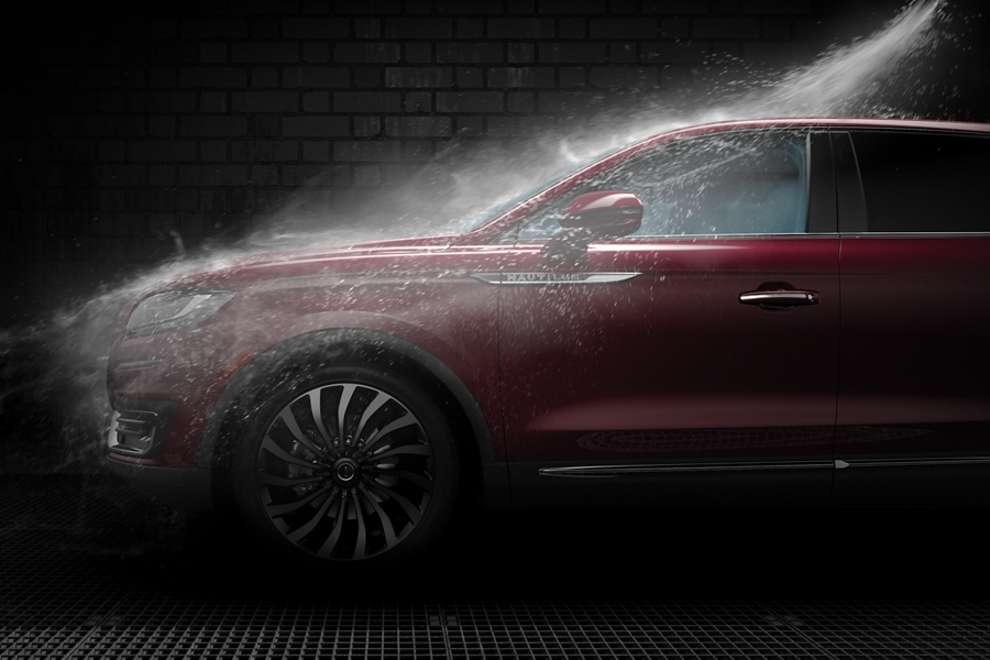 A fine spray of water mist showers a vehicle in a car wash