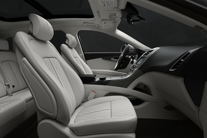 A side view shows the front passenger and drivers seats in the mainly white Chalet theme with dark wood inlays