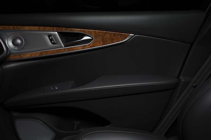 The front passenger door is shown from the interior highlighting Jet Black leather and rich real wood inlays