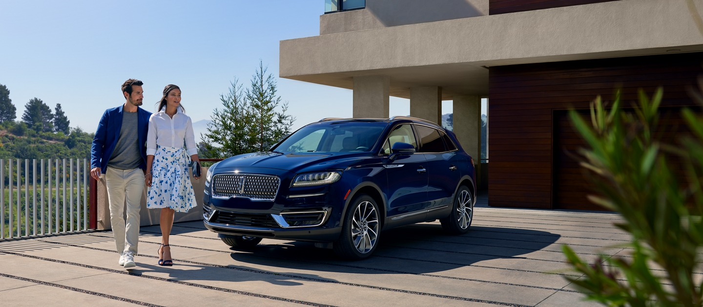 A 2020 Lincoln Nautilus shown in the Rhapsody Blue exterior color is parked in the driveway of a modern hillside home