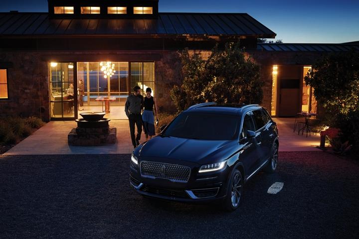 Una pareja se aproxima de noche a la Lincoln Nautilus 2020 mientras Lincoln Embrace se enciende y les indica el camino hacia el vehículo