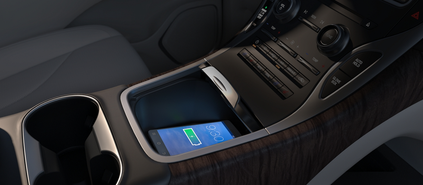 A smartphone rests on the Available wireless charging pad in the front media bin of a 2020 Lincoln Nautilus