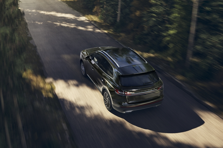 A 2020 Lincoln Nautilus is shown being driven along a forest lined road to demonstrate the adaptive suspension