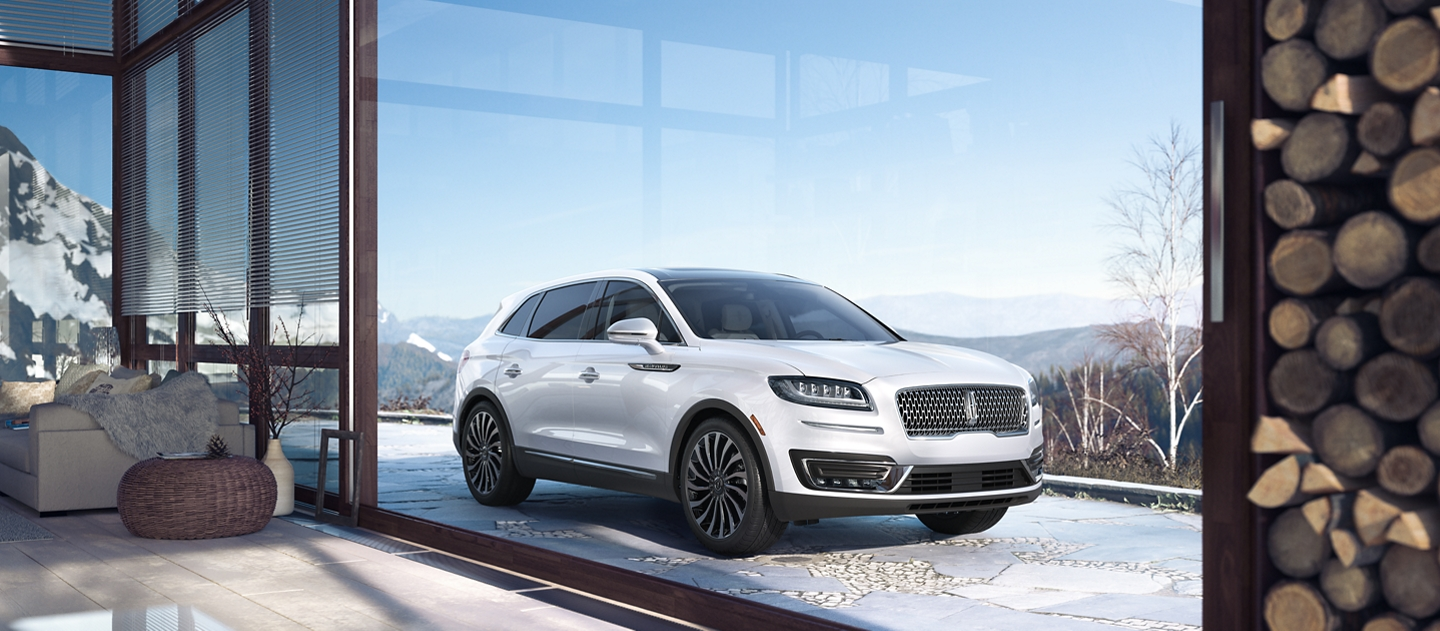 A 2020 Lincoln Black Label Nautilus in the Chalet theme is shown parked in the driveway of a luxurious mountain home
