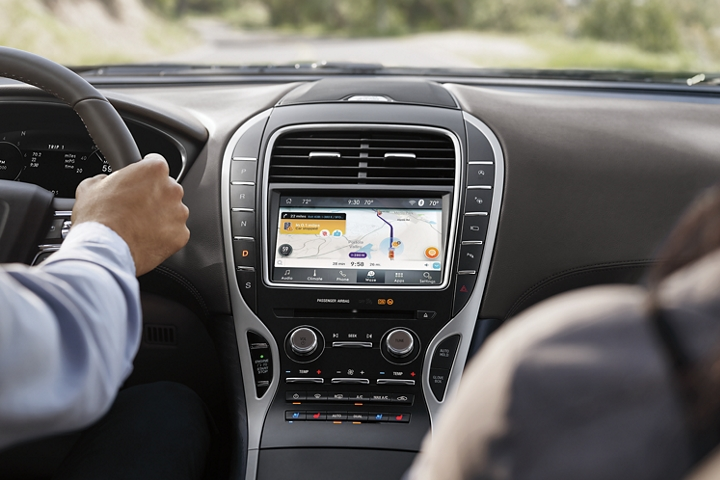 A waze app screen is shown in the touchscreen in the center console