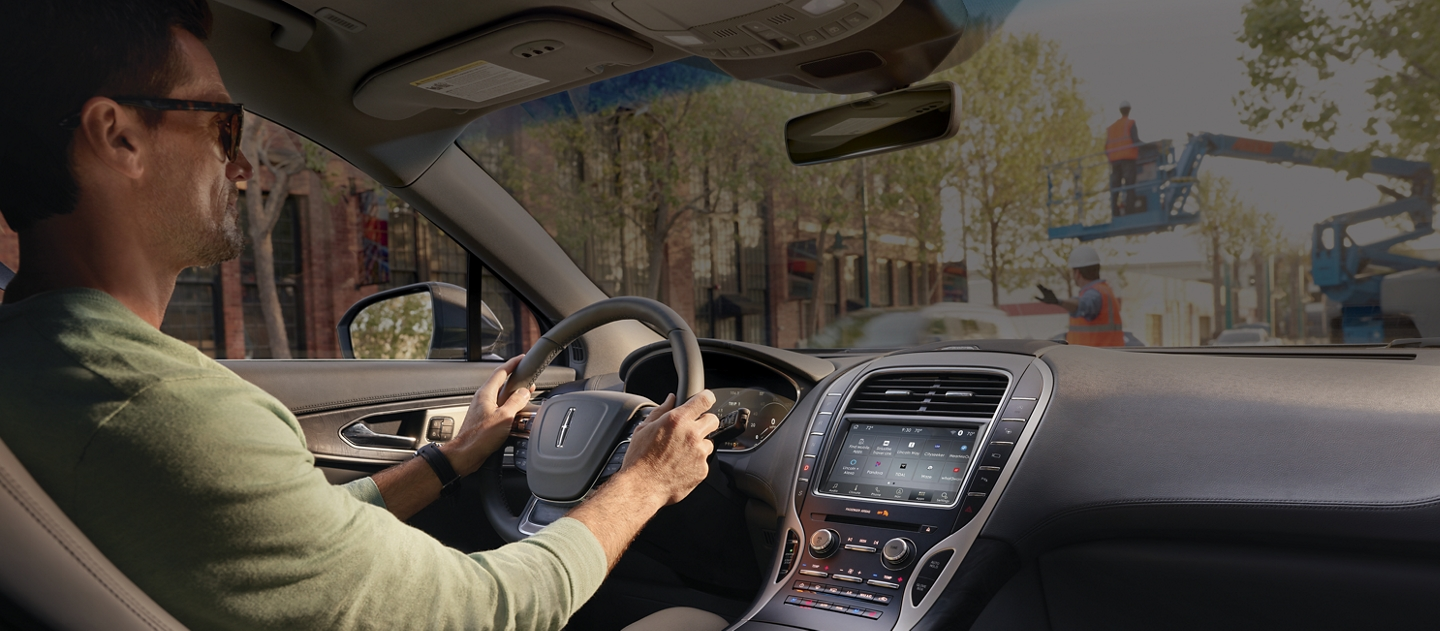 A person is shown behind at the steering wheel of a 2020 Lincoln Nautilus as a noisy scene is shown through the windshield