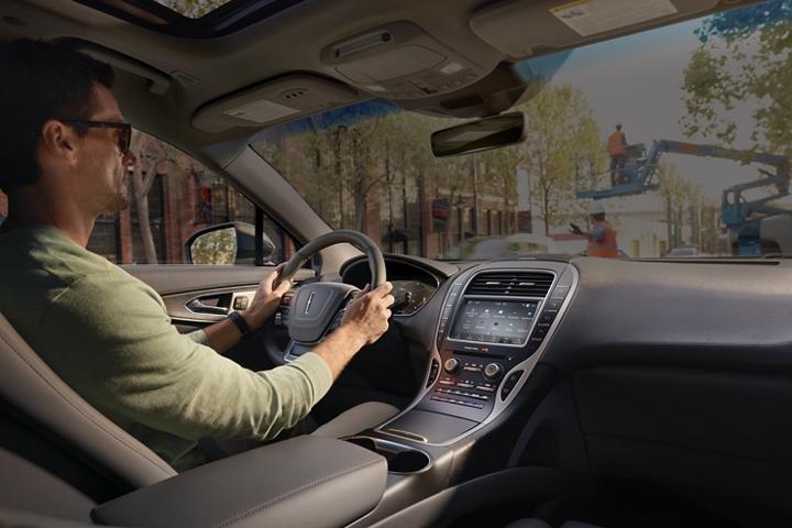 Un hombre está sentado en el asiento del conductor de la Lincoln Nautilus 2020 mientras se observa por el parabrisas la imagen de una obra en construcción ruidosa