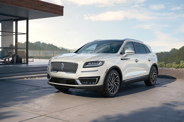 A 2020 Lincoln Nautilus in the Pristine White exterior color is shown parked in the driveway of a contemporary home