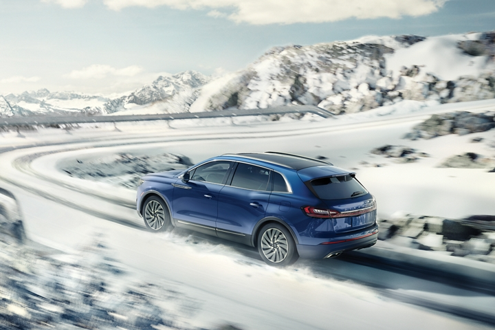 A 2020 Lincoln Nautilus is shown being driven on a snow covered road with a sharp turn ahead
