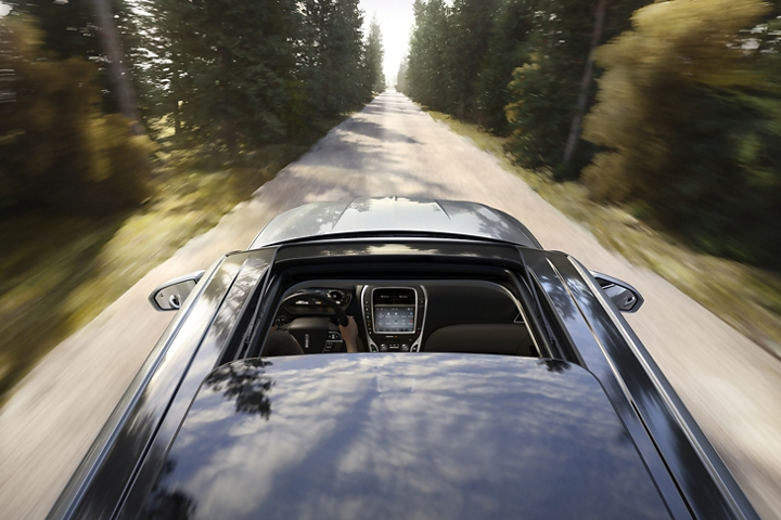 A 2020 Lincoln Nautilus is shown being driven along a tree lined road with an available panoramic Vista Roof wide open