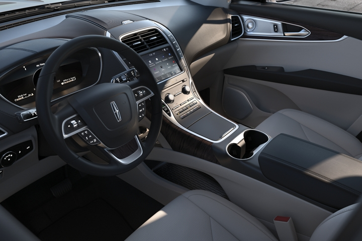 The steering wheel and center stack of a 2020 Lincoln Nautilus are shown as seen from the drivers point of view as they enter the vehicle