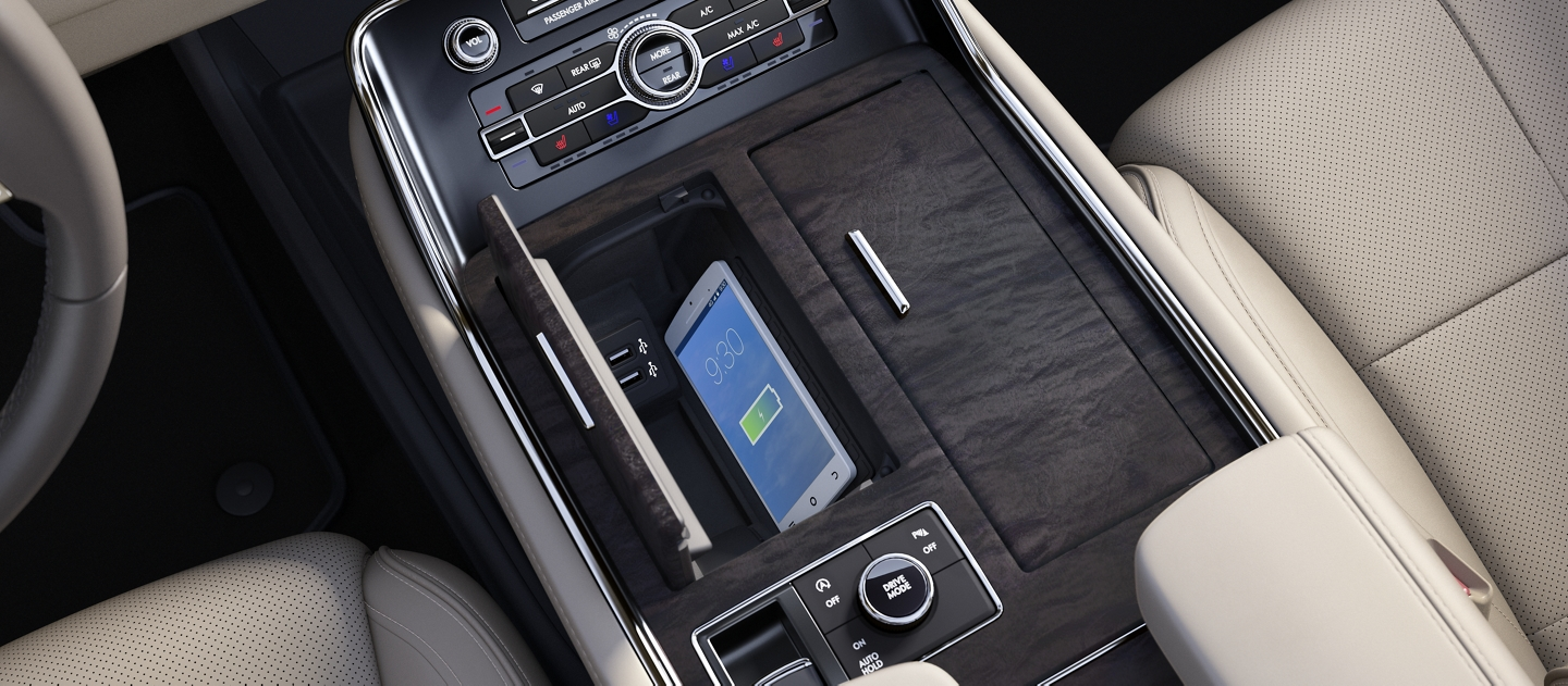 A compatible mobile phone is shown charging on the available inductive charging system within the center console