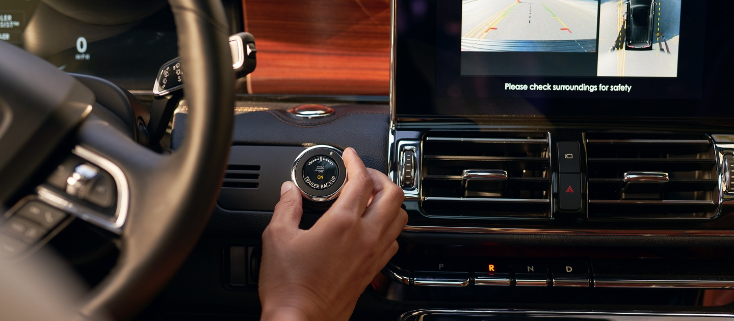 A hand is shown using a knob to steer a navigator equipped with the available Heavy Duty Trailer Tow Package