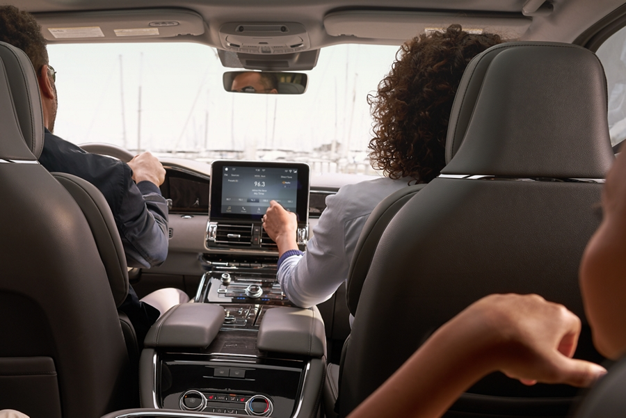 A woman is shown using the center consoles touchscreen to control the temperature inside a Lincoln Navigator