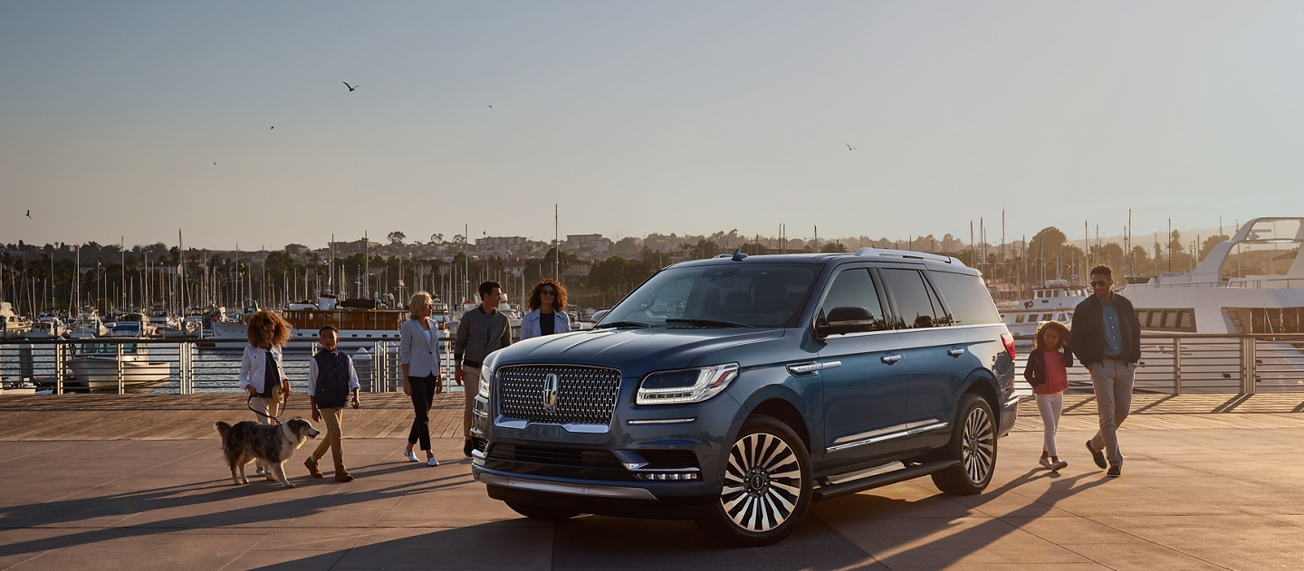 Family and friends are shown approaching a Lincoln Navigator in a marina setting