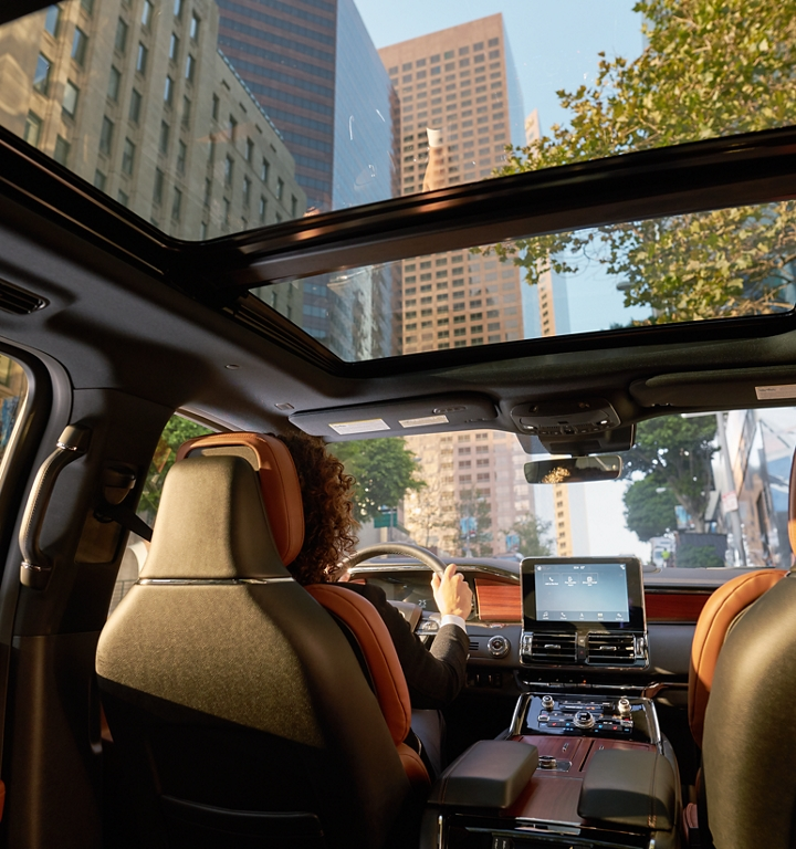A city scene is shown through the available panoramic Vista Roof from inside a Lincoln Navigator