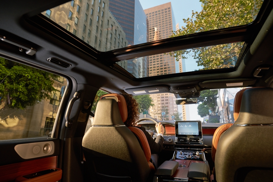 A city scene is shown through the windshield and panoramic Vista Roof of a Lincoln Navigator