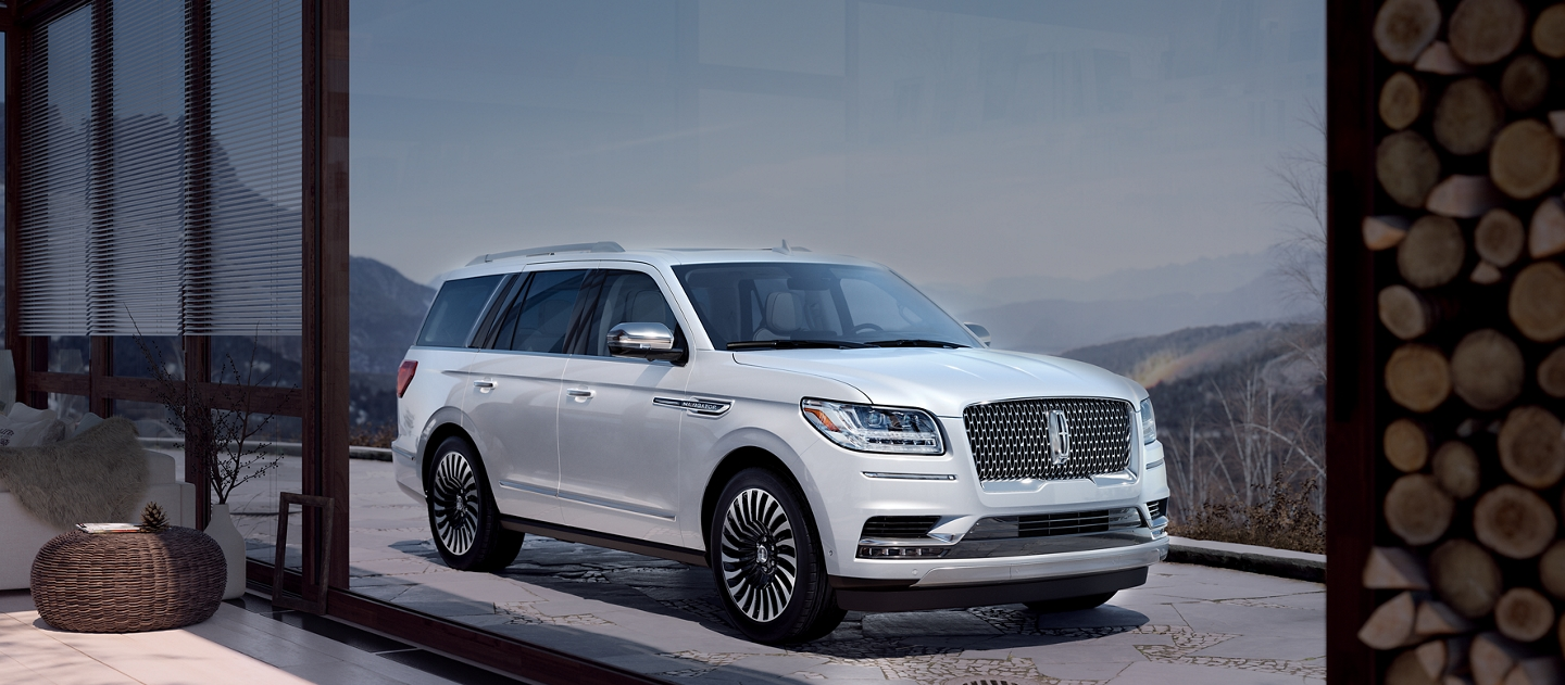 A Lincoln Black Label Navigator in the Chalet theme is shown parked in the driveway of a luxurious mountain home