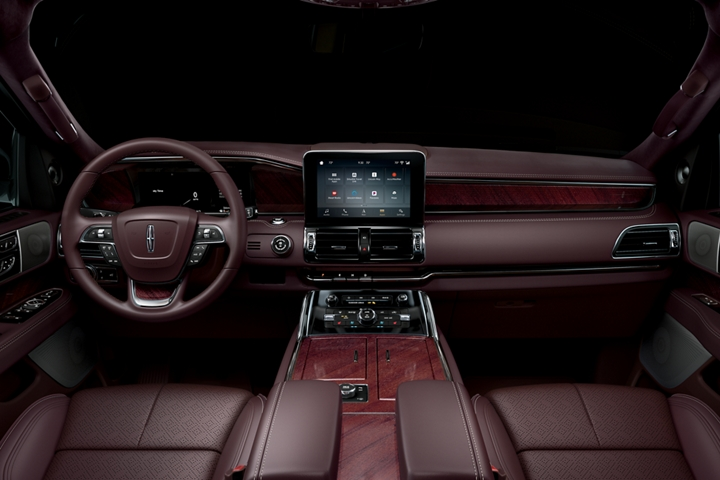 An interior view of the front row of a Lincoln Black Label Navigator in the Destination theme shows rich leather and wood detail
