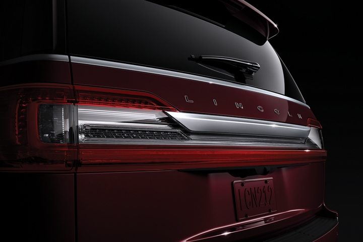 The rear of a Lincoln Navigator is shown in the Burgundy Velvet Metallic exterior color associated with the Destination theme