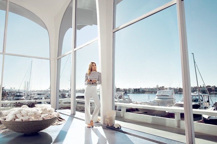 A woman is shown inside of a Yacht Club looking out toward the marina