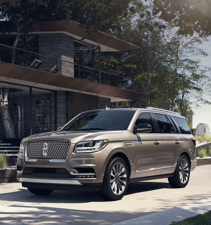 A Lincoln Navigator seen in the Iced Mocha exterior color is parked in the driveway of a modern home