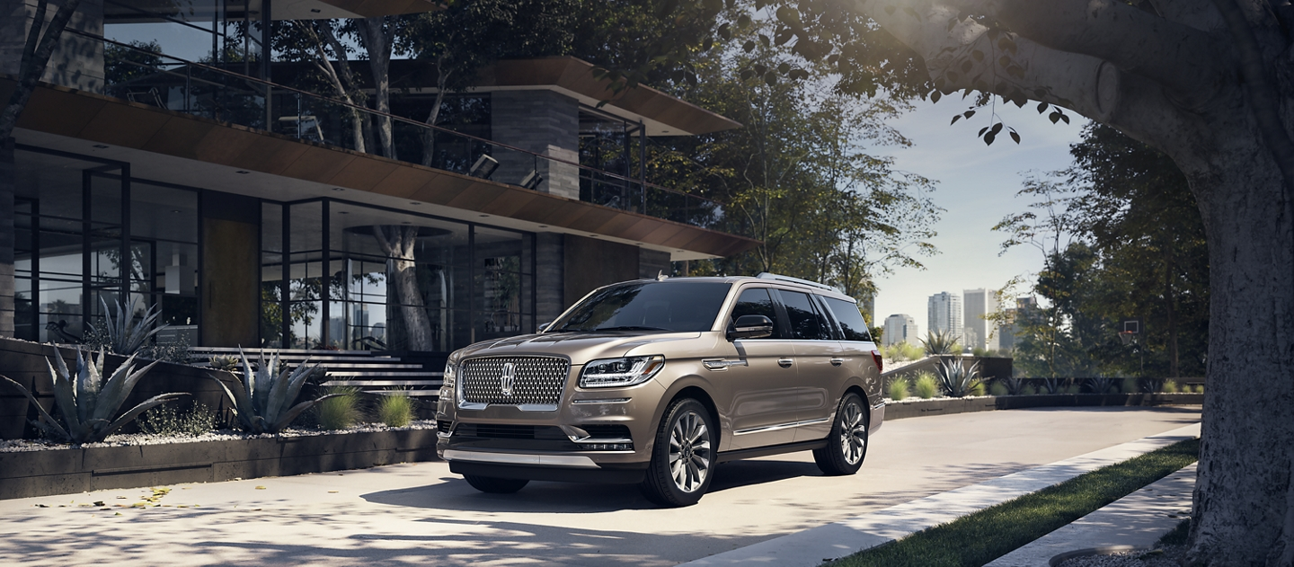 The Lincoln Navigator parked in front of a modern home is shown in the Iced Mocha exterior color