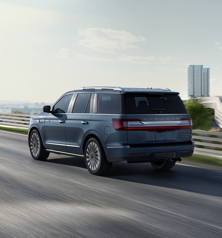 A Lincoln Navigator is seen driving on a highway with a cityscape in the background