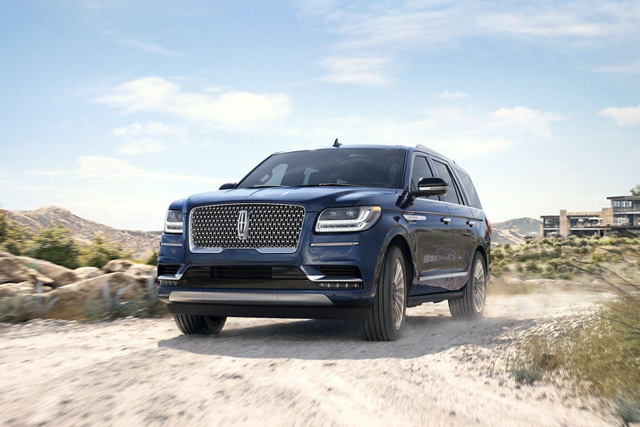 A resort is shown in the background while a Lincoln Navigator shown in the Rhapsody Blue exterior color is being driven away