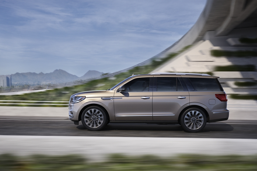 The Lincoln Navigator shown in the Iced Mocha exterior color is seen being driven under an overpass