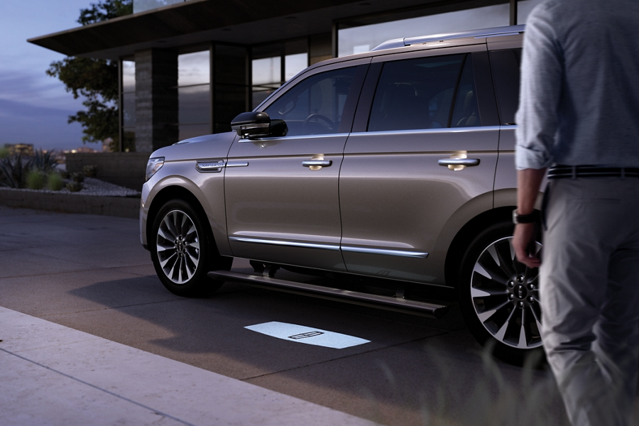 A person approaches a Lincoln Navigator while an illuminated Lincoln logo welcome mat is projected onto the ground