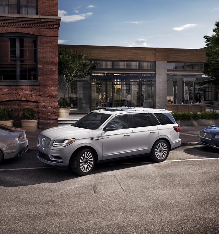 A Lincoln Navigator is being parallel parked to simulate how the available active park assist system works