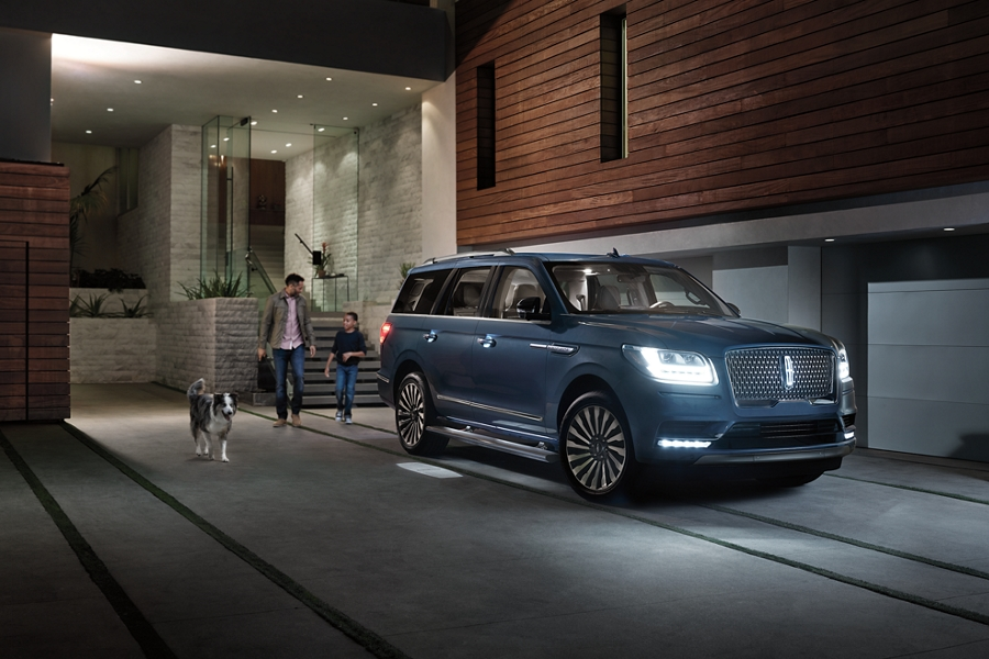 An illuminated Lincoln logo welcome mat is shown as it is projected on the ground from a Lincoln Navigator